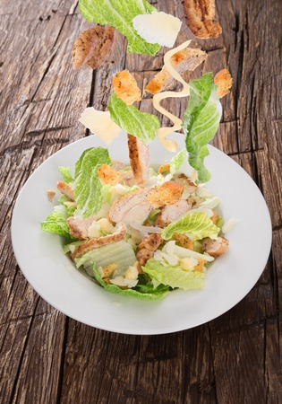 the greens: Caesar salad with chicken and greens on wooden table