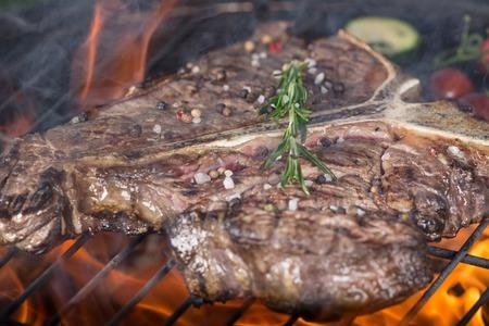 Delicious beef t-bone steak on garden grill, close-up photo