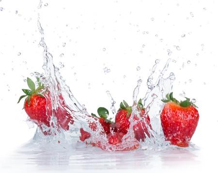白い背景の上の水のしぶきと新鮮なイチゴ