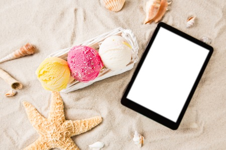 Ice cream scoops with tablet on sandy beach, close-up.