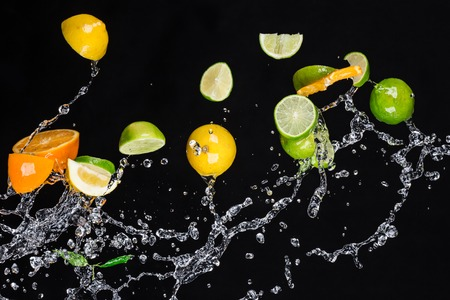 Fresh fruit with water splash on black background