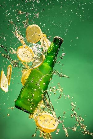 green beer bottle: Green beer bottle with splashing liquid, freeze motion.