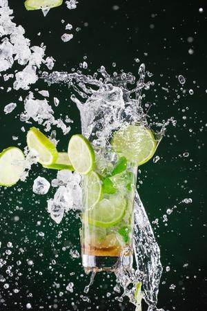 bar: fresh mojito drink with liquid splash and drift, freeze motion. Stock Photo