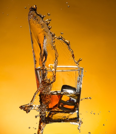 whisky glass: Whiskey with ice with liquid splash, freeze motion.