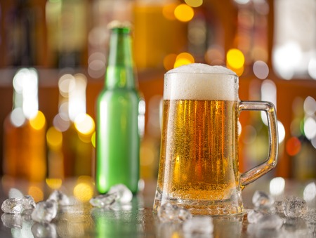 glass beer bottle: Bottle of beer with glass on bar desk, close-up.