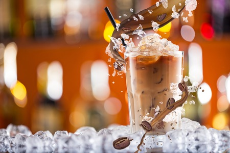 bebidas frias: Frío beber café con hielo, frijoles y salpicaduras, primer plano.
