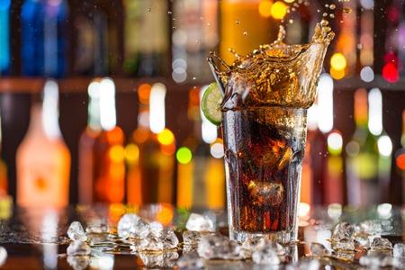 Glass of cola on bar desk with splashing liquid, close-up.