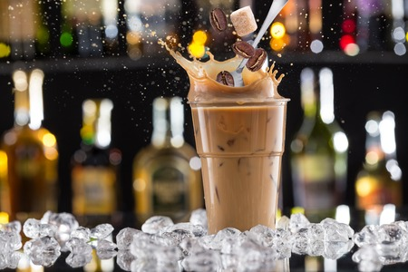 frio: Frío beber café con hielo, frijoles y salpicaduras, primer plano.
