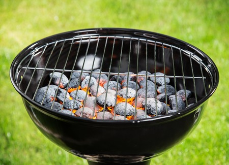 briquettes: Garden grill with blistering briquettes, close-up. Stock Photo