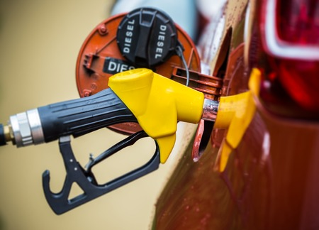 refilling: Hand refilling the car with fuel, close-up.