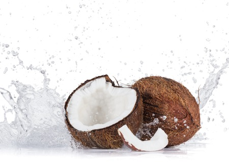 Cracked coconuts with water splash on white background, close-up. Stock Photo
