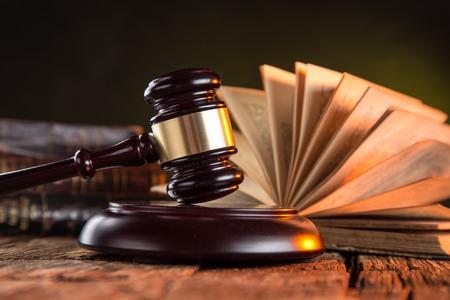 documentos legales: Mazo de madera y libros sobre la mesa de madera, concepto de Derecho