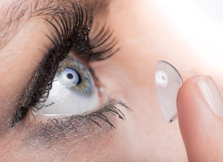 yeux: Jeune femme Insertion d'une lentille de contact, close-up Banque d'images