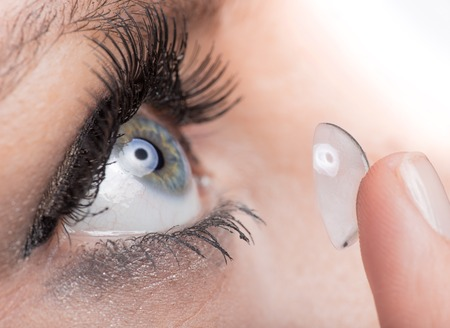 softness: Young woman Inserting a contact lens, close-up Stock Photo