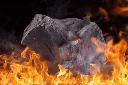 carbon emission: Piles of coals with fire flames. Stock Photo