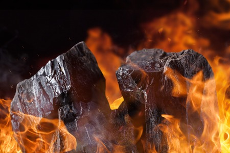 coal fire: Piles of coals with fire flames. Stock Photo