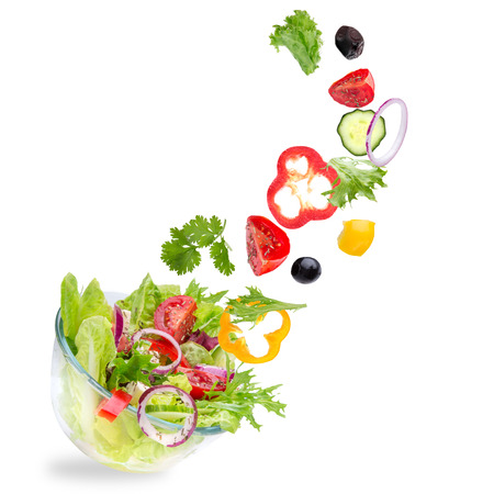 salad plate: Fresh salad with flying vegetables ingredients isolated on a white background.