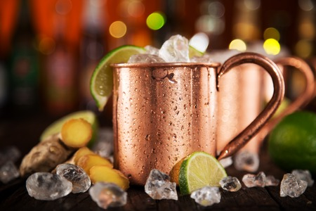cocktail drinks: Cold Moscow Mules - Ginger Beer, lime and Vodka on bar Stock Photo