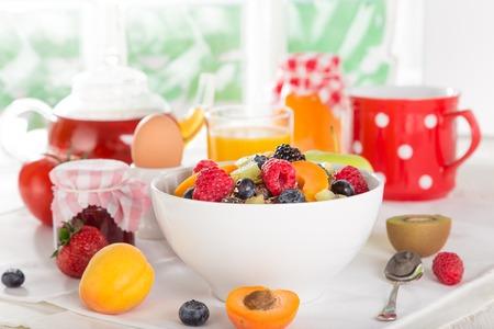 glass bowl: Healthy breakfast with muesli, fruit, tea and berries