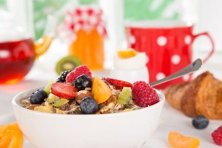 Gezond ontbijt met muesli, fruit, thee en bessen