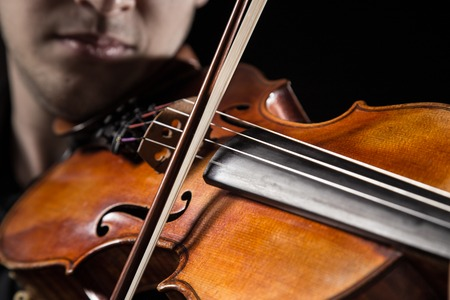 solo violinist: Young man with violin on dark background