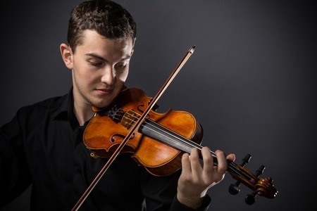 violin background: Young man with violin on dark background
