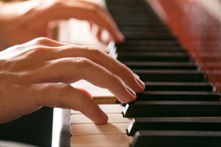 playing piano: Close-up of hands playing the piano Stock Photo