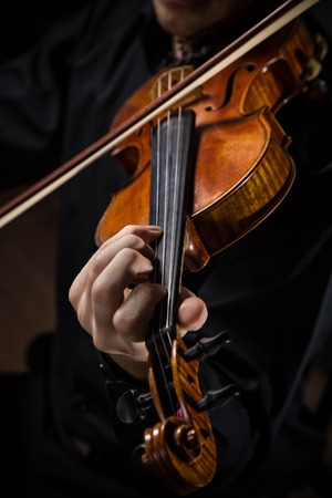 fiddlestick: Young man with violin on dark background