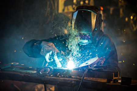 Welder in action with bright sparks Reklamní fotografie - 43157514