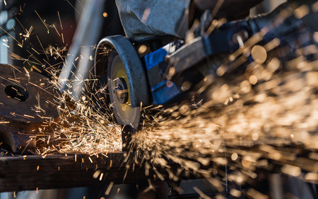 welding mask: Grinding machine in action with bright sparks Stock Photo