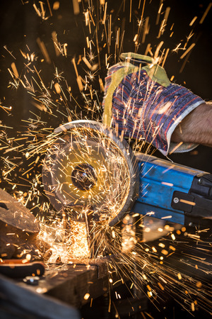 skilled: Grinding machine in action with bright sparks Stock Photo