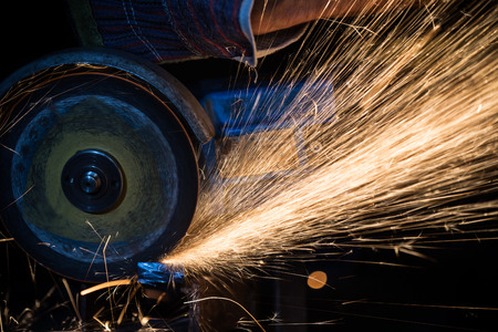 skilled labour: Grinding machine in action with bright sparks Stock Photo
