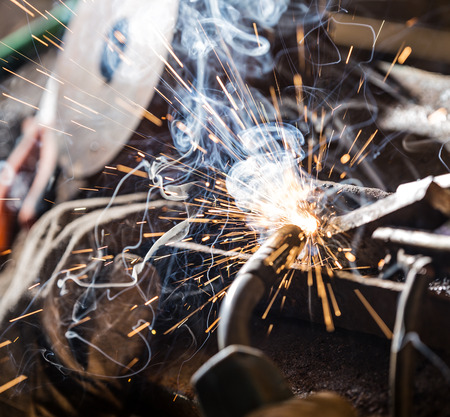 skilled: Welder in action with bright sparks