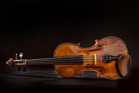 Old vintage violin on black background.