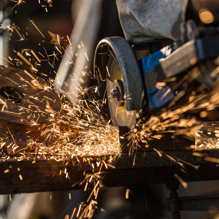 industrial equipment: Grinding machine in action with bright sparks Stock Photo