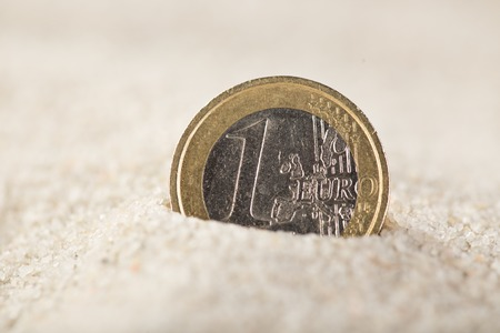 Euro coin in the sand, close-up.