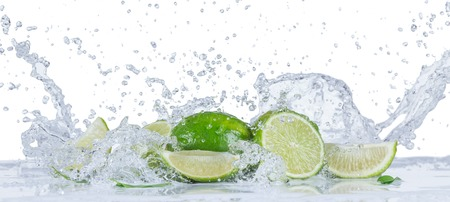Verse limes met waterspatten geïsoleerd op een witte achtergrond