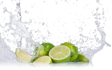 Fresh limes with water splashes isolated on white background