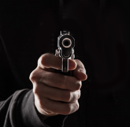 Killer with gun close up over dark background.