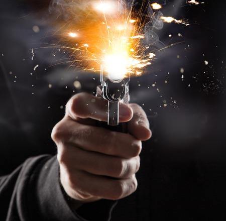 Killer met pistool close-up over een donkere achtergrond.