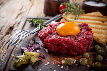 steak tartare: Close up of beef tartar with capers and small toasts. Stock Photo