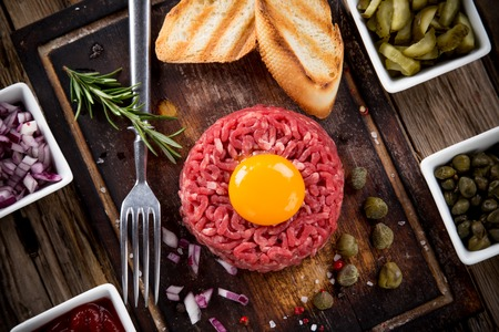 Close up of beef tartar with capers and small toasts. Stock Photo