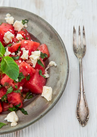 feta cheese: Fresh salad with water-melon, feta cheese, lime and mint, close-up.