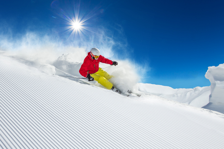 Skier skiing downhill during sunny day in high mountains 版權商用圖片 - 45149201