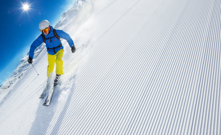 downhill: Skier skiing downhill during sunny day in high mountains