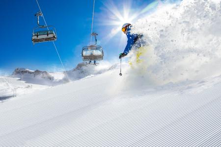 Skifahrer Skifahren bergab im sonnigen Tag in den hohen Bergen Lizenzfreie Bilder