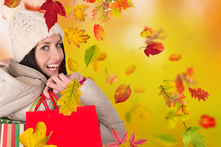 happy shopping: Beautiful woman holding shopping bags, buying in autumn season. Happy female shopper.