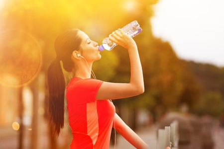Young woman drinking water after running in the city. Female fitness model training outside in Prague. Stock Photo