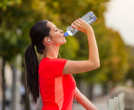 woman running: Young woman drinking water after running in the city. Female fitness model training outside in Prague. Stock Photo
