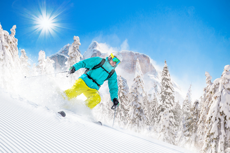 downhill: Skier skiing downhill in high mountains